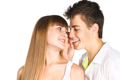 Teen boy whispering in his girlfriend's ear. Closeup portrait of a handsome boy whispering in his girlfriends ear isolated over white stock photo