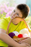 Teen boy with wicker basket and balls of yarn Royalty Free Stock Photography