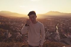 Teen boy wipe the eye in front of the city of Prizren, Kosovo in Stock Photos