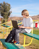 Teen Boy  Working on Laptop. Cute teen aged boy sitting on bleachers working on his laptop Stock Photography