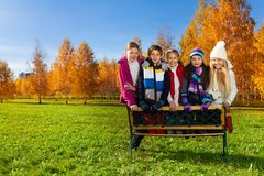 Teen boys and girls stand on the bench Stock Image