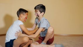 Teen boys with hands and faces in colorful paints sitting on floor play with each other royalty free stock photography