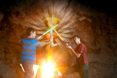 Teen Boys Join Light Swords. Three teen boys join light swords to create a star flare in a composited image Royalty Free Stock Photography