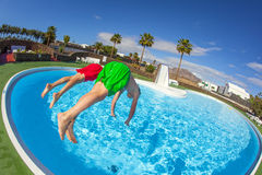 Teen boys jumping in the blue pool. Boy has fun jumping in the pool Stock Image