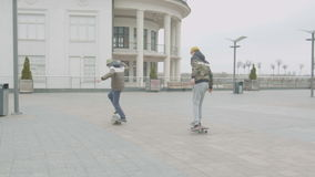 Teen boys rolling skates practicing doing tricks. Teenage skaters learning to do rolling off a drop and manual tricks skateboarding on city street. Warmly stock footage
