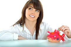 Teen brunette. Young girl who puts money in a piggy bank Royalty Free Stock Images