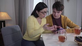 Teen brunette Caucasian boy teaching adult mother in eyeglasses to use smartphone. Patient son helping woman to deal