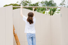 Teen Builds Shed. Teen girl working on building a shed Stock Photos