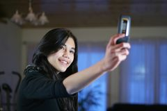 Teen with a camera phone. Young teen girl taking her own picture with camera phone Royalty Free Stock Photos