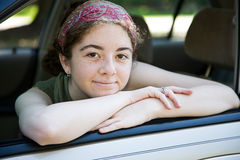 Teen in Car Window. Pretty teen girl leaning out the drivers window of her car Stock Photography