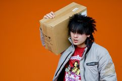 Teen carrying cardboard box. A view of a young boy carrying a medium size cardboard box over his shoulder.  Isolated on orange background Stock Image