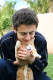 Teen and cat. Teen hugging red and white cat Stock Image