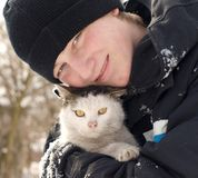 Teen and cat. Winter portrait - young man-teen-with a dirty cat, smiling in the winter nature Stock Photography