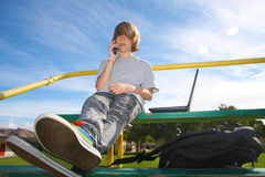 Teen with cell phone on bleachers. Young teen aged boy talking on cell phone, sitting on bleachers with a laptop beside him Royalty Free Stock Photo