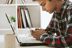 Teen on cellphone and laptop. Teen boy using cellphone sitting at laptop keyboard on desk inside home office Stock Photography