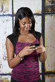 Teen on cellphone texting. Smiling young African American teenager looking at cell phone texting Royalty Free Stock Image