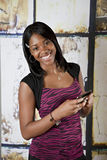 Teen on cellphone texting. Smiling young African American teenager smiling while holding cell phone Royalty Free Stock Images