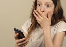 Shocking phone message disturbs girl. Teen checks her phone, and discovers a message that she finds unsettling stock photo