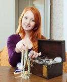 Teen  chooses jewelry in treasure chest Stock Photo