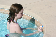Teen cleaning pool edge. Teen girl cleaning the edge of a pool royalty free stock image