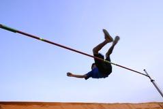 Teen clearing high jump bar. An athlete falling over the high jump bar with a pastel blue sky. Motion blur present. Below is a orange mattress Stock Photo
