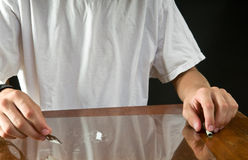 Teen cocaine use. Teenage boy making a line of cocaine with razor blade on glass Royalty Free Stock Image