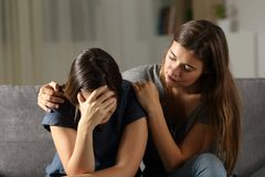 Teen comforting hes sad friend in the night. Sitting on a couch in the living room at home Stock Images