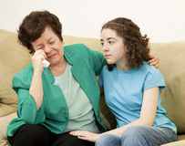Teen Comforts Mother. Teenage girl tries to comfort her crying mother stock image