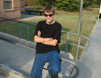 Teen Cool. A relaxed teenaged boy in sunglasses sits outside and looks cool to the world Stock Images