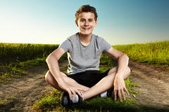 Teen on a countryside road. Outdoor portrait of a teenager boy sitting in the middle of a rural dirt road Stock Photos