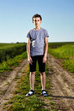 Teen on a countryside road. Outdoor portrait of a teenager boy standing in the middle of a rural dirt road Stock Photos