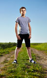 Teen on a countryside road. Outdoor portrait of a teenager boy standing in the middle of a rural dirt road Royalty Free Stock Photography