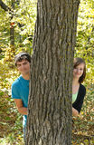 Teen Couple. A teen couple peeking out from behind a tree in the forest stock images