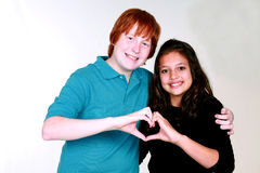 Teen Couple with Boy Blushing. Teen caucasian couple with boy blushing making a heart with hands Royalty Free Stock Image