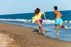 Teen couple chasing on beach. Royalty Free Stock Photos