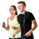 Teen couple doing fitness workout together. Close up portrait of active teen couple doing fitness workout together.Couple jogging together with smart phones and Royalty Free Stock Photography