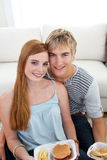 Teen couple eating burgers and fries on the floor. At home Stock Photography