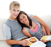 Teen couple eating burgers and fries at home. Teen couple eating burgers and fries on the sofa at home Royalty Free Stock Photos