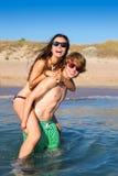Teen couple enjoying  piggyback on summer beach. Shore splashing water Stock Photography