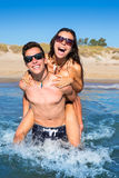 Teen couple enjoying  piggyback on summer beach. Shore splashing water Royalty Free Stock Photography