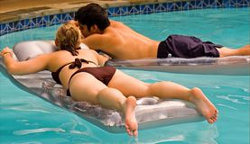 Teen couple floating in pool. A view of a young teenage couple relaxing as they lay on blow-up floats in a backyard pool on a hot summer day Royalty Free Stock Image