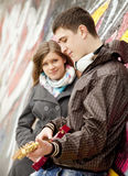Teen couple with guitar at graffiti background.  stock photos