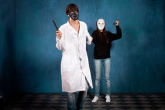 Teen couple with halloween masks and knifes. In blue room Stock Photos