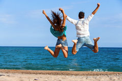 Teen couple jumping giving backs. Rear view of Teen couple jumping and raising arms on beach royalty free stock photography