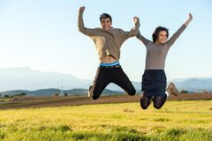 Teen couple jumping outdoors. Royalty Free Stock Photos
