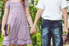 Teen couple, little girl and boy holding his hand. First love or Stock Photo