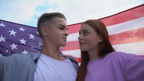 Teen couple in love touching foreheads holding american flag, young patriots stock video footage
