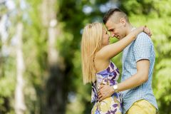 Teen couple in the park. Teen couple embracing in the park royalty free stock photography
