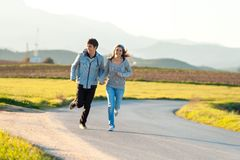 Teen couple running in countryside. Stock Photos