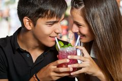 Teen couple sharing cocktail. Royalty Free Stock Photo